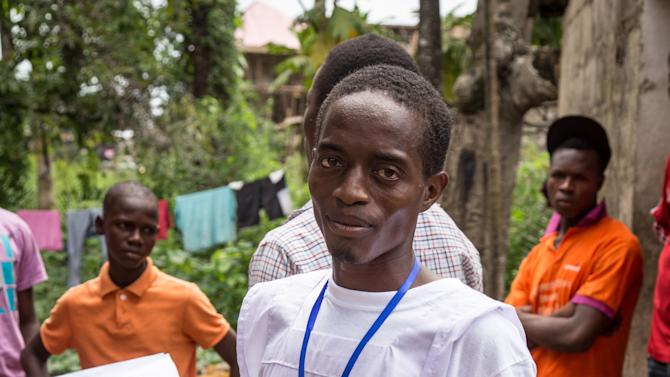 In this Sept. 19, 2014 photo,  Idrissa Kargbo, Sierra Leone's National marathon champion who took part in the New York marathon, in recent years, joins Ebola volunteers going from house to house to look for Ebola virus patients in Freetown, Sierra Leone, Thousands of health workers began knocking on doors across Sierra Leone on Friday in search of hidden Ebola cases with the entire West African nation locked down in their homes for three days in an unprecedented effort to combat the deadly disease. (AP Photo/ Michael Duff)