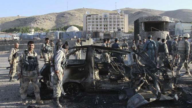 Afghan security forces inspect a damaged car, which was used during a suicide bomb attack, outside the U.S. consulate in Herat province