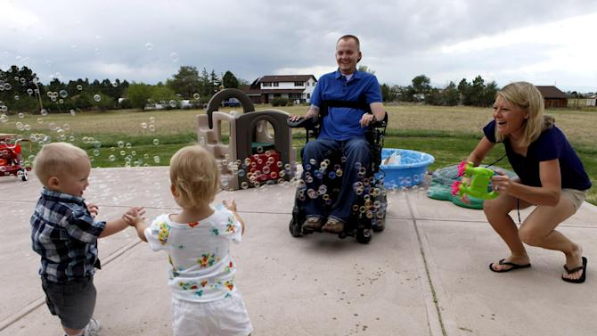 This photo taken Aug. 2, 2012, shows the Keil family playing with a bubble machine at their home near Parker, Colo. From left are; Matthew Jr., Faith, Matthew and Tracy. A bill being considered in the Senate would expand the VA's medical benefits package so other veterans, and their spouses or surrogates, don't have to bear the same expense. The department currently covers a range of medical treatment for veterans, including some infertility care, but the legislation would authorize the VA to cover the cost of IVF and to pay for procedures now covered for some critically injured active-duty soldiers. (AP Photo/Ed Andrieski)