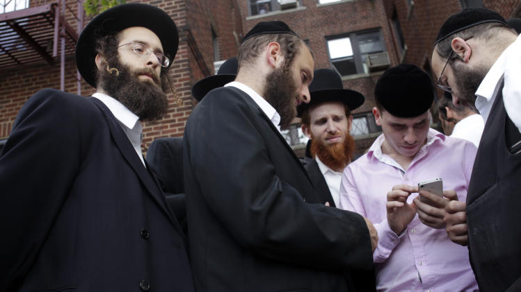 Members of the orthodox Jewish community gather around Shimon Jacobowitz, in pink shirt, who shows a picture on his phone of a man he believes to be the perpetrator in the murder of a recently missing boy in the Brooklyn borough of New York, Wednesday, July 13, 2011.  Remains believed to be those of Leiby Kletzky, 8, who disappeared while walking home from a Brooklyn day camp were found in a refrigerator Wednesday inside the home of a man being questioned by detectives, police said.  (AP Photo/Seth Wenig)
