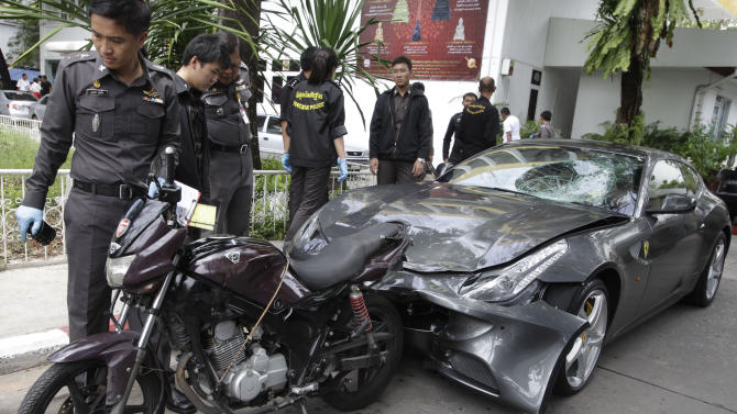 In this photo taken Sept. 3, 2012, Thai police officers look at a motorcycle and a Ferrari car that involved in a hit-and-run accident during the investigation at Thong Lor police station in Bangkok, Thailand. A grandson of the creator of the Red Bull energy drink has been arrested for driving the Ferrari that struck a police officer and dragged his dead body down a Bangkok street in an early-morning hit-and-run, police said Monday. (AP Photo)