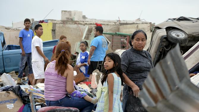 Residents recover belongings from their damaged house after a tornado hit the town of Ciudad Acuna