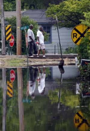 Residents of Kings Community in Vicksburg, Miss., walk along the raised railroad tracks late Thursday, May 12, 2011 as their images are reflected in the waters of the Mississippi River that has flooded the mainly African-American community. (AP Photo/Rogelio V. Solis)