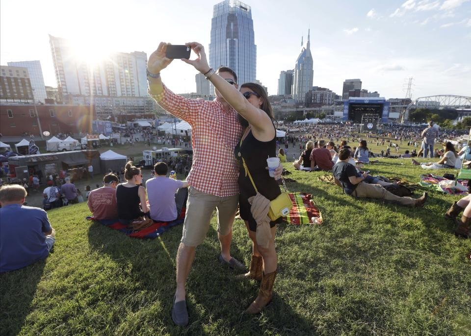 In this Sept, 28, 2013 photo, a couple takes a picture of themselves as they attend an outdoor concert at the Southern Ground Music & Food Festival on Sept. 28, 2013, in Nashville, Tenn. The festival is part of a growing link between Nashville's music and food scenes. (AP Photo/Mark Humphrey)