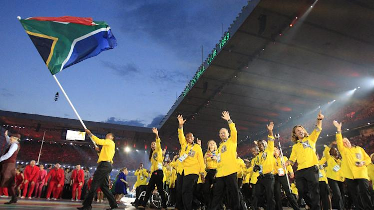 South Africa's flag bearer Cecil Sebastian Afrika leads the team into the arena during the opening ceremony for the Commonwealth Games 2014 in Glasgow, Scotland, Wednesday July 23, 2014. (AP Photo/Frank Augstein)
