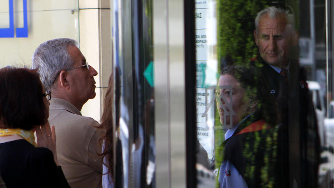 Private security officers stand at a main door of a bank as people wait outside of a cooperative bank in capital Nicosia, Cyprus, on Friday, March 29, 2013. Banks in Cyprus are open for normal business for the second day, but with strict restrictions on how much money their clients can access, after being shut for nearly two weeks to prevent people from draining their accounts as the country's politicians sought a way out of an acute financial crisis. (AP Photo/Petros Karadjias)