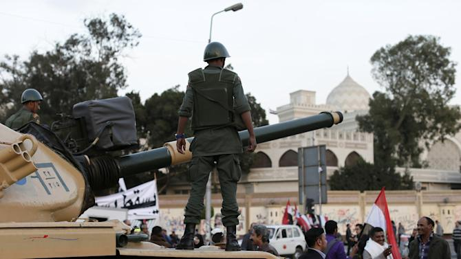 An Egyptian protester takes a picture with his mobile of another in front of an Egyptian army tank outside the presidential palace, background, in Cairo, Egypt, Saturday, Dec. 8, 2012. Egypt's military warned Saturday of 'disastrous consequences' if the crisis that sent tens of thousands of protesters back into the streets is not resolved, signaling the army's return to an increasingly polarized and violent political scene.(AP Photo/Hassan Ammar)
