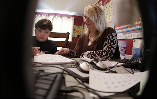In this Tuesday, Jan. 22, 2013 photo, Devon Carrow works with teacher Sheri Voss while attending school from home while operating a robot in the classroom, in Orchard Park N.Y. Carrow's life-threateni