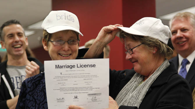 """Claudia Gorbman, left, and partner Pam Keeley wear caps both reading """"bride"""" as they display their newly-issued marriage license, Thursday, Dec. 6, 2012, in Seattle. King County Executive Dow Constantine  began issuing the licenses immediately upon certification of the November election that passed Referendum 74. (AP Photo/Elaine Thompson)"""