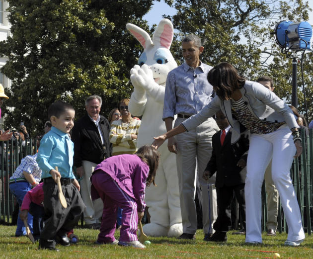 President Barack Obama and first lady Michelle Obama watch as children participate in the annual Easter Egg Roll on the South Lawn of the White House in Washington, Monday, April 1, 2013. (AP Photo/Su