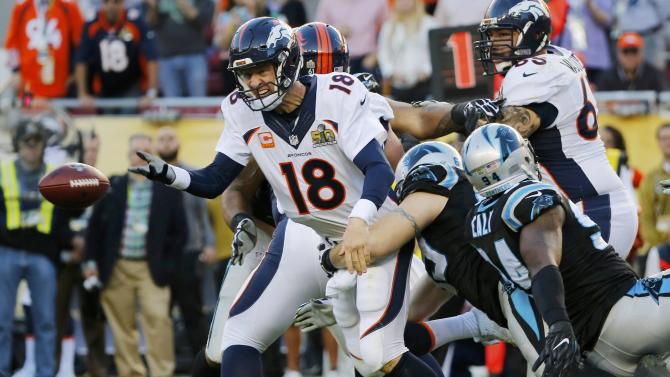 Denver Broncos' quarterback Peyton Manning flips the ball forward as he is tackled by Carolina Panthers' defenders during the second quarter of the NFL's Super Bowl 50 football game in Santa Clara