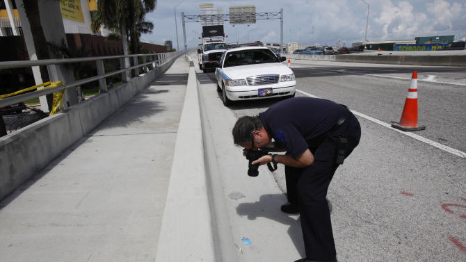 Crime Scene investigator Andres Betancourt photographs a credit card found at the scene belonging to Rudy Eugene, Tuesday, May 29, 2012 in Miami. Authorities were seeking more witnesses Tuesday to help explain what led Eugene, who was naked, to start chewing another naked man's face and whose only response when confronted by police was to growl and keep attacking - even after being shot by police Saturday. (AP Photo/Wilfredo Lee)