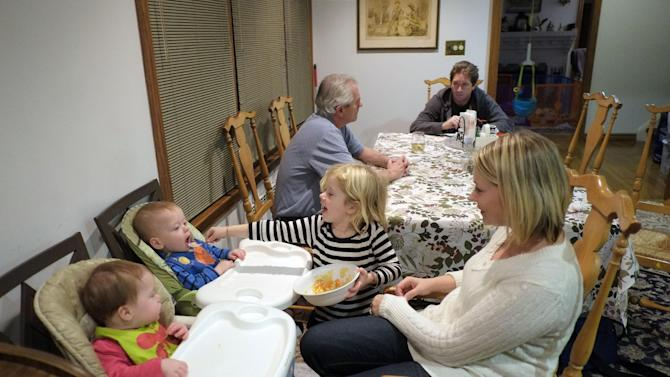 In this Tuesday, Dec. 4, 2012 photo, Lauren Mullaney watches as her daughter, Keira, 4, helps to feed 10-month-old twins Devin, left, and Patrick at their rental home in the Marine Park section of New York. Mullaney's father, Frank O'Neill, and brother Tommy O'Neill talk in the background. Mullaney's home was among more than 100 burned in a massive fire in the Breezy Point neighborhood of New York during Superstorm Sandy on Oct. 29. Frank O'Neill also lives in Breezy Point and his home was severely damaged by flooding during the storm. (AP Photo/Mark Lennihan)