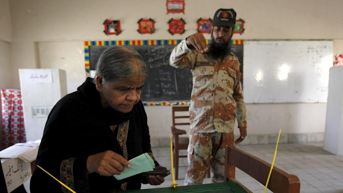 A Pakistan paramilitary personnel assists a voter during municipal by-elections in Karachi