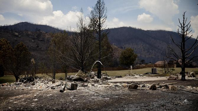 "The remains of a burned structure are left in the Mountain Shadow neighborhood devastated by raging wildfires, Friday, June 29, 2012, in, Colorado Springs, Colo. After declaring a ""major disaster"" in the state early Friday and promising federal aid, President Obama got a firsthand view of the wildfires and their toll on residential communities. More than 30,000 people have been evacuated in what is now the most destructive wildfire in state history. (AP Photo/Carolyn Kaster)"