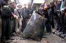 FILE - This January 19, 2014, file photo provided by Aleppo Media Center (AMC), an anti-Bashar Assad activist group, which has been authenticated based on its contents and other AP reporting, shows Syrian citizens inspecting an unexploded barrel bomb filled with explosives, which was dropped from a Syrian forces helicopter on a street in Aleppo, Syria. The use of barrel bombs has spread this year from Syria to Iraq, raising concerns that desperate governments in a number of unstable nations from Europe to Africa to the Middle East will turn to weapons that the international community has condemned as a violation of human rights laws. (AP Photo/Aleppo Media Center, AMC, File)