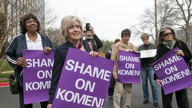 FILE - In this Feb. 7, 2012 file photo, a small group of women protest outside the Susan G. Komen for the Cure headquarters in Dallas. Several high-ranking executives with Susan G. Komen for the Cure have resigned in the aftermath of Komen's decision earlier this year to eliminate most of its funding for Planned Parenthood. Although some of the officials cited personal reasons, the resignations suggest the breast cancer charity is still in turmoil, even after restoring the money. (AP Photo/Rex C. Curry, File)