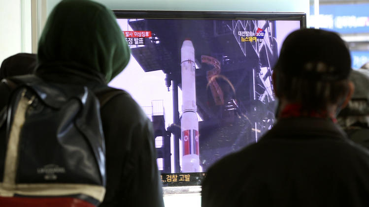 South Koreans watch a TV news program about North Korea's rocket launch plans at Seoul Railway Station in Seoul, South Korea, Sunday,  Dec. 9, 2012. North Korea may postpone the controversial launch of a long-range rocket that had been slated for liftoff as early as this week, state media said Sunday, as international pressure on Pyongyang to cancel the provocative move intensified. (AP Photo/Ahn Young-joon)