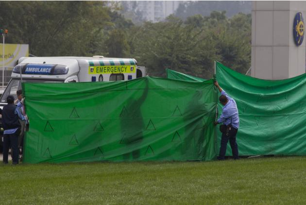 Staff members from the Jockey Club form a screen around paramedics as they tend to British jockey Steve Drowne after he fell off his horse in Hong Kong