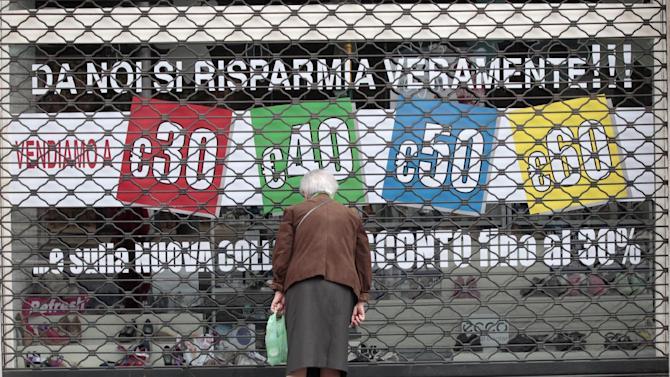 """A woman looks through a shuttered shop window reading: """"here you can really save your money"""" during May Day in Rome, Tuesday, May 1, 2012. Italian Premier Mario Monti has promised to get Italy's economy growing again, but so far his government has been widely criticized by industrialists and union leaders for failing to revive growth. (AP Photo/Gregorio Borgia)"""
