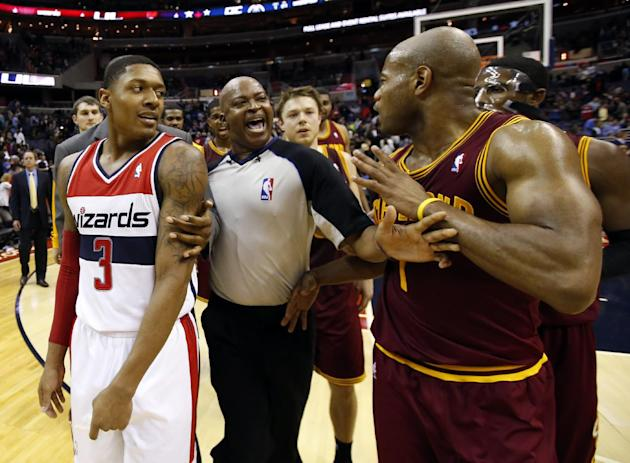 Washington Wizards guard Bradley Beal (3) and Cleveland Cavaliers guard Jarrett Jack (1) are separated by a referee after an NBA basketball game on Saturday, Nov. 16, 2013, in Washington. The Cavalier