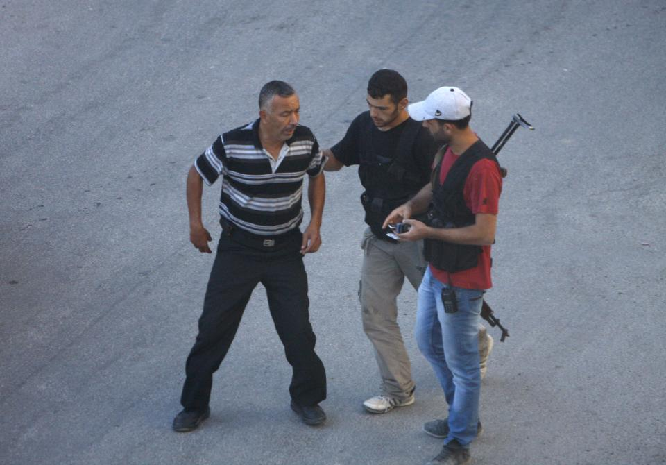 In this Thursday Aug. 2, 2012 photograph, Syrian rebel fighters detain a man at an improvised checkpoint in a suburb of Damascus, Syria. (AP Photo)