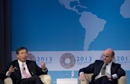 Yi Gang (L), Deputy Governor of the People's Bank of China, speaks alongside Luis de Guindos, Minister of Economy and Competitiveness of Spain, during a CNN Debate on the Global Economy at George Washington University on October 10, 2013