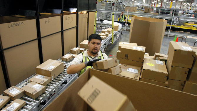 FILE - In this Nov. 11, 2010 file photo, Ricardo Sandoval places packages in the right shipping boxes at an Amazon.com fulfillment center, in Phoenix. Products are flying off the shelves at Amazon warehouses across the county as Californians prepare to start paying sales taxes on online purchases. The change, which takes effect Saturday, Sept. 15, 2012, will pave the way for the e-commerce giant to open warehouses in California and offer same-day shipping to customers.  (AP Photo/Ross D. Franklin, file)