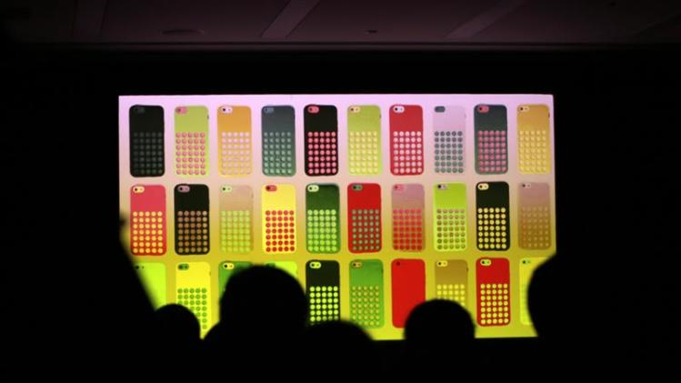 Journalists watch a screen showing the new iPhone 5C in different colours at Apple Inc's announcement event in Beijing