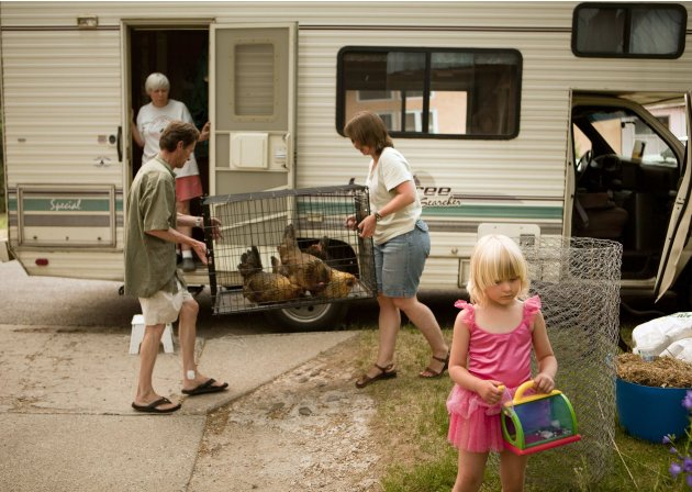 The Morrison family, Dee, top left, Taylor, 4, right, Bob, and Jeni, center, pack up their belongings following a mandatory evacuation ordered for Los Alamos, N.M., as the rapidly-growing Las Conchas