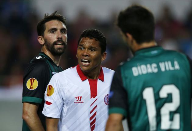 Sevilla's Carlos Arturo Bacca reacts between Real Betis' players during their Europa League soccer match in Seville