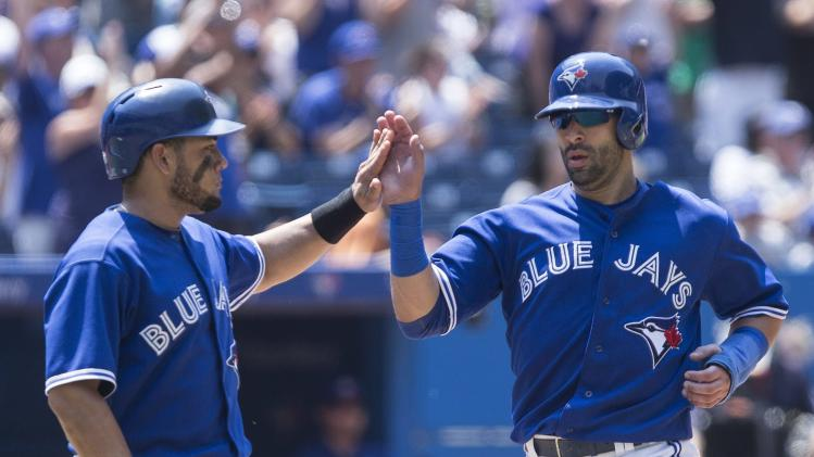 Toronto Blue Jays' Jose Bautista, right, and Melky Cabrera celebrate scoring on an RBI-double by Edwin Encarnacion against the Baltimore Orioles during third-inning baseball game action in Toronto, Sunday June 23, 2013. (AP Photo/The Canadian Press, Chris Young)