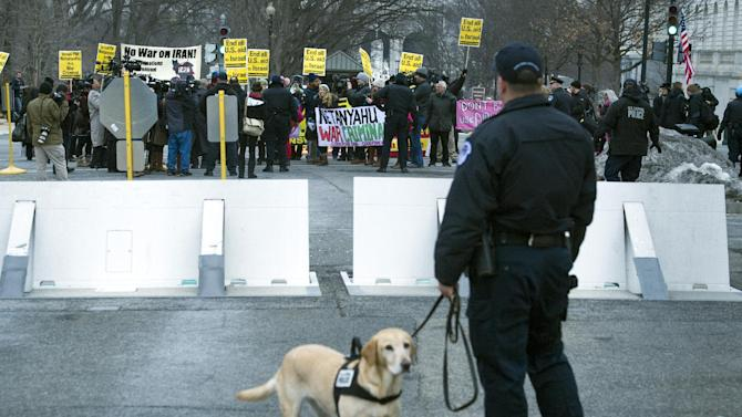"""A Capitol Hill police officer watches as an anti-Israel protesters march on Capitol Hill in Washington, Tuesday, March 3, 2015, before Israeli Prime Minister Benjamin Netanyahu's address to a joint meeting of Congress. In a speech that stirred political intrigue in two countries, Netanyahu told Congress that negotiations underway between Iran and the U.S. would """"all but guarantee"""" that Tehran will get nuclear weapons, a step that the world must avoid at all costs. (AP Photo/Cliff Owen)"""