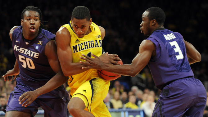 Michigan's Glenn Robinson III drives to the basket between Kansas State's D.J. Johnson, left, and Martavious Irving, right, during the first half of an NCAA college basketball game in the championship game of the NIT Season Tip-Off tournament at Madison Square Garden in New York, Friday, Nov. 23, 2012.  (AP Photo/Bill Kostroun)