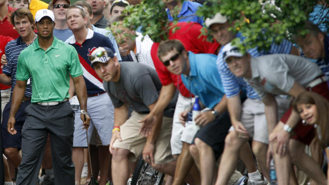 Fans stretch to get a looks after Tiger Woods, left, hit from the rough on the fifth hole during the second round of the Wells Fargo Championship golf tournament at Quail Hollow Club in Charlotte, N.C., Friday, May 4, 2012. (AP Photo/Nell Redmond)