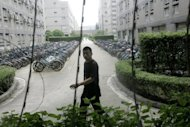 A Chinese worker is seen walking through the dormitory area of a Foxconn factory in, southern China&#39;s Guangdong province in 2010. Apple, following reports of harsh working conditions, said the watchdog Fair Labor Association began inspections at a Foxconn plant in China that makes products for the California gadget-maker