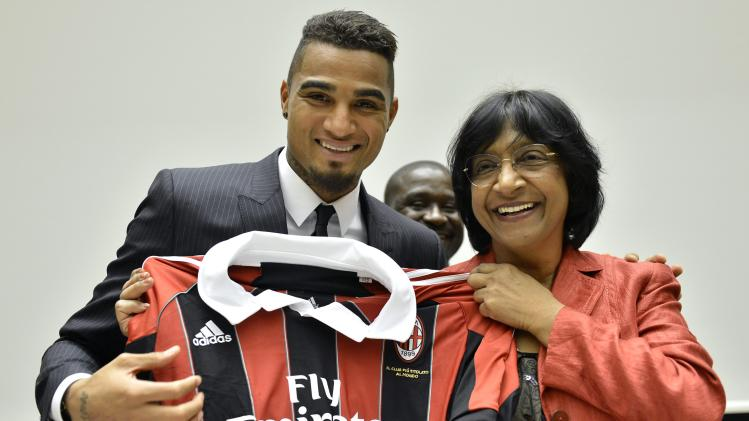 Kevin-Prince Boateng, left, soccer player for AC Milan Football Club  and  U.N. High Commissioner for Human Rights, South African Navanethem Pillay, right, pose with an AC Milan jersey after a panel discussion on Racism and Sport, during the World Humanitarian Day, at the European headquarters of the United Nations in Geneva, Switzerland, Thursday, March 21, 2013.  (AP Photo/Keystone,Martial Trezzini)