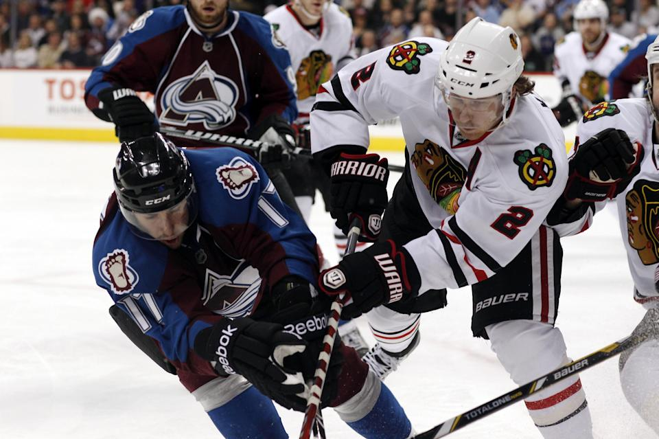 Colorado Avalanche right wing Aaron Palushaj, left, battles for control of the puck with Chicago Blackhawks defenseman Duncan Keith in the third period of the Avalanche's 6-2 victory in an NHL hockey game in Denver on Friday, March 8, 2013. The Blackhawks lost in regulation for the first time this season.  (AP Photo/David Zalubowski)