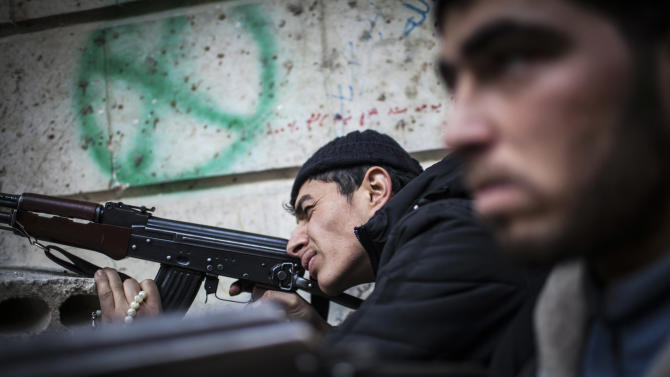 A Free Syrian Army fighter aims his weapon in Aleppo, Syria, Tuesday, Jan. 15, 2013. Two explosions struck the main university in the northern Syrian city of Aleppo on Tuesday, causing an unknown number of casualties, state media and anti-government activists said. (AP Photo/Andoni Lubaki)