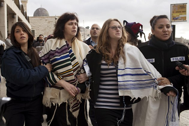 Wrapped in Jewish prayer shawls, Rabbi Susan Silverman, second left, the sister of comedian Sarah Silverman, not seen, along with her teenage daughter Hallel Abramowitz, second right, are detained by police officers in Jerusalem's Old City, Monday, Feb. 11, 2013. The head of the Women of the Wall organization, a liberal Jewish women's group, said 10 women were detained for wearing religious garb which Orthodox Judaism reserves for men only. About 300 people gathered at the Western Wall Monday to protest the Orthodox Jewish control of the site. (AP Photo/Tali Mayer)