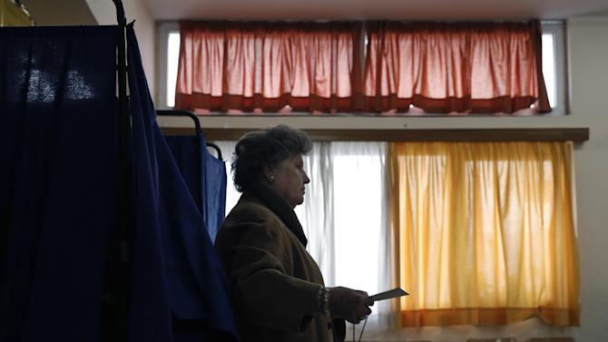 A woman casts his vote at a polling station in Athens, Sunday, Jan. 25, 2015. Greeks were voting Sunday in an early general election crucial for the country's financial future, with the radical left Syriza party of Alexis Tsipras tipped as the favorite to win, although possibly without a large enough majority to form a government. (AP Photo/Petros Giannakouris)