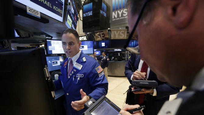 Specialist Jason Hardzewicz, left, works at his post on the floor of the New York Stock Exchange Tuesday, July 8, 2014. U.S. stocks are opening lower for a second day in a row as investors position themselves for corporate earnings reports. (AP Photo/Richard Drew)