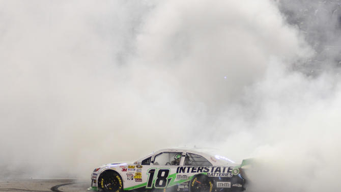 Sprint Cup Series's Kyle Busch (18) celebrates after winning the NASCAR Sprint Cup series NRA 500 auto race at Texas Motor Speedway  Saturday, April 13, 2013, in Fort Worth, Texas.(AP Photo/Larry Papke)
