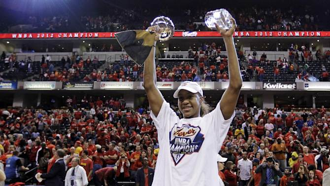 Indiana Fever forward Tamika Catchings celebrates with the trophy and the MVP award after winning the WNBA basketball Finals against the Minnesota Lynx in Indianapolis, Sunday, Oct. 21, 2012. The Fever won 87-78 to clinch their first WNBA championship. (AP Photo/Michael Conroy)