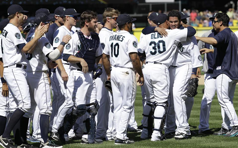 Teammates congratulate Seattle Mariners pitcher Felix Hernandez, second from right, after he threw a perfect game against the Tampa Bay Rays, Wednesday, Aug. 15, 2012, in Seattle. The Mariners defeated the Rays 1-0 in the baseball game. (AP Photo/Ted S. Warren)