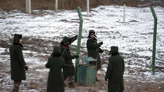 In this Saturday, Dec. 8, 2012 photo, Chinese paramilitary policemen build a fence near a crossing into North Korea at the Chinese border town of Tumen in eastern China's Jilin province. Over the past year, Kim Jong Un has intensified a border crackdown that has attempted to seal the once-porous 1,420-kilometer (880-mile) frontier with China, smugglers and analysts say, trying to hold back the onslaught.(AP Photo/Ng Han Guan)