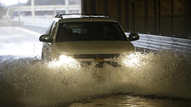 """In a Jan. 17, 2013 photo, a Chevrolet Suburban is driven through the flood test at the General Motors Milford Proving Grounds in Milford, Mich.  It's in this northwest Detroit suburb that GM has its testing facility, which, according to GM consumer affairs chief James Bell, exists for the purpose of beating """"the heck out of a vehicle before the customer can."""" Founded in 1924, the 4,000-acre Milford Proving Grounds was the first dedicated automotive testing facility in the world, and remains one of the largest to this day. (AP Photo/Carlos Osorio)"""
