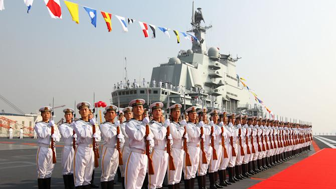 """FILE - In this Sept. 25, 2012 file photo provided by China's Xinhua News Agency, sailors stand at attention on the deck of China's aircraft carrier """"Liaoning"""" in Dalian, northeast China's Liaoning Province, as China formally entered its first aircraft carrier into service. As President Barack Obama tours Southeast Asia to push his year-old pivot to the Pacific policy, the big question on everybody's mind is how much of a role Washington, with its mighty military and immense diplomatic clout, can play in keeping the Pacific peaceful. (AP Photo/Xinhua, Zha Chunming, File) NO SALES"""