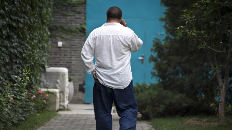 Ai Weiwei talks on his mobile phone as he walks in his house's courtyard in Beijing Wednesday, June 20, 2012. Chinese police on Wednesday barred Ai from attending the first hearing of a lawsuit brought by his company against Beijing tax authorities and blocked reporters from filming at the courthouse, part of an intimidation campaign aimed at silencing the prominent artist and outspoken government critic. (AP Photo/Andy Wong)