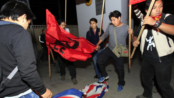 Demonstrators step on a British flag during a protest outside the United Kingdom's embassy in Quito, Ecuador, Wednesday, Aug. 15, 2012. Ecuador accused Britain on Wednesday of threatening to storm its London embassy to arrest Julian Assange after the U.K. issued a stern warning to the South American nation ahead of its decision on an asylum bid by the WikiLeaks founder. People protested against the alleged threat. (AP Photo/Dolores Ochoa)